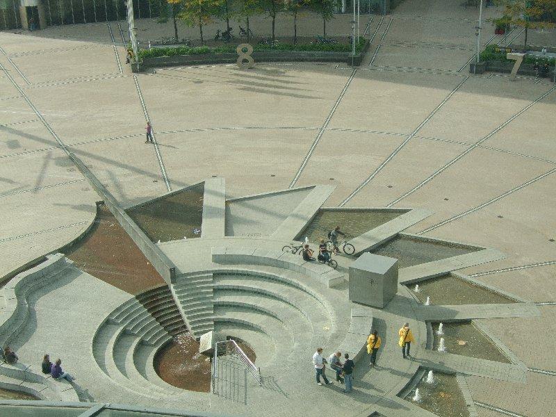 Der Brunnenplatz des Mediaparks mit mannshohen Hausnummern vor den im Halbrund errichteten Gebäuden