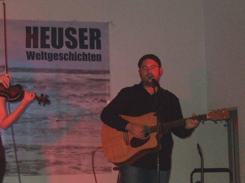 "Björn Heuser vor dem Plakat zum Programm ""zom Zohüüre"""