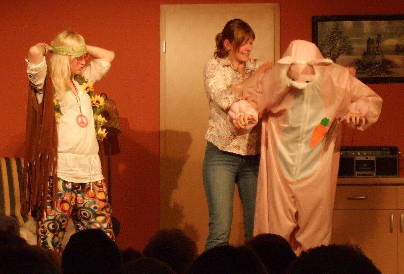 Mia Fastnacht (Angelika Mangold) hilft Oliver, dem Neffen der Nachbarn (Florian Schmitz) ins unauffällige Hasenkostüm, während die Tochter (Sarah Haake) sich als Hippie verkleidet.