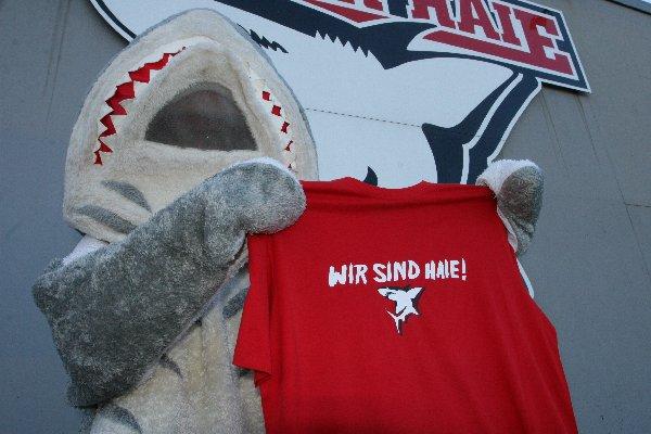 """Das Haie-Maskottchen präsentiert das """"Rettershirt"""" das bei der Abwendung der Insolvenz helfen soll"""