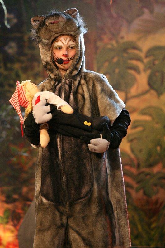 Der Panther Drüggela (Jovina Fischer) bringt das kleine Hänneschen zur Wolfsmutter (Man beachte die Kölsche Mütze), Foto: Kemper