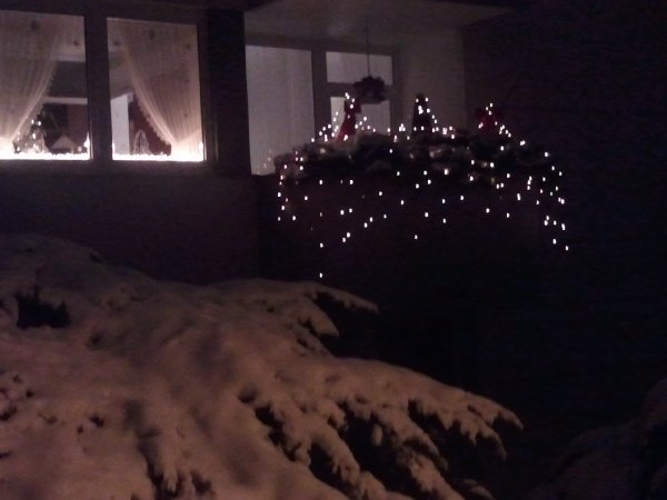 Beispiel eines weihnachtlich geschmückten Balkons neben erleuchtetem Fenster