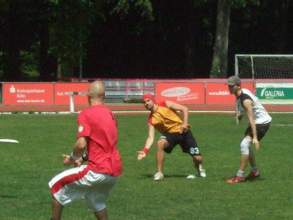 Jens Gerhards bei der Spieleröffnung mit dem Vorhandpass auf Tob Morat, rechts Martin Bierwirth in der Verteidigung