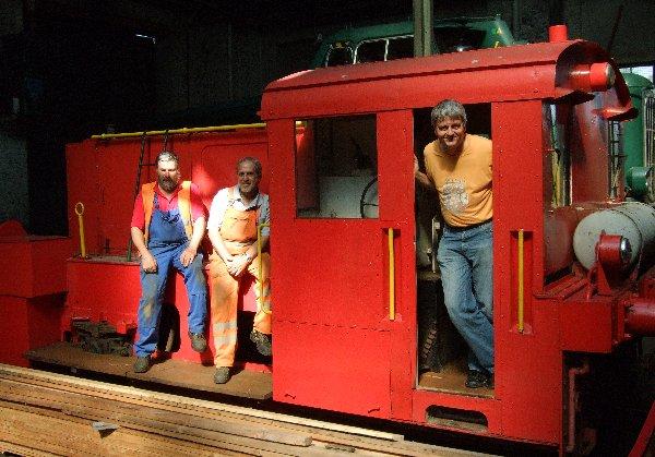 """Kassenwart Jörg Seidel (r.), 2. Vorsitzender Peter Stapper (l.) und Harry Braun vom RIM e.V. auf einer alten Kölner Lok, mit der Trümmer vom Neumarkt geräumt wurden, später bei """"Bios Bahnhof"""" zu sehen."""